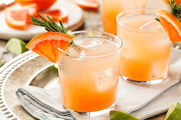 Refreshing Grapefruit and Tequila Palomas Refreshing Grapefruit and Tequila Palomas with Rosemary garnish stock pictures, royalty-free photos & images