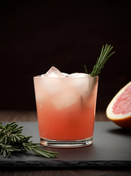 refreshing grapefruit cocktail with rosemary on dark background. - grapefruit cocktail stock photos and pictures