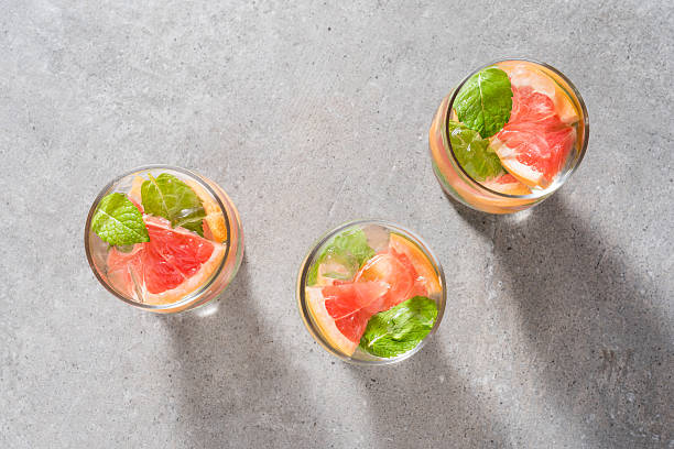 refreshing grapefruit drink with mint leaves and ice - grapefruit cocktail stock photos and pictures