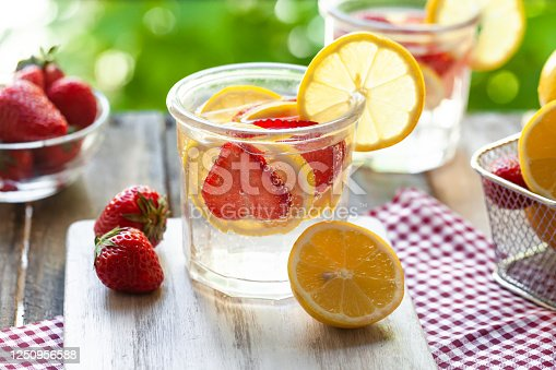 Refreshing homemade lemonade with fresh strawberry, lemon and ice. Healthy cold drink, low calories. Tasty cool summer beverage. Wooden white background, two glasses. Macro, close up