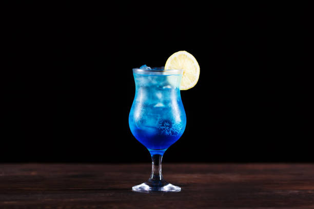 Refreshing iced blue alcoholic cocktail with lemon slice, cold drink, party, bar concept stock photo