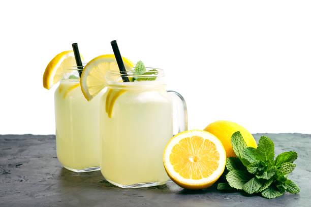 在黑暗的桌子和白色的背景的罐子裡, 用檸檬片和薄荷清涼檸檬水飲料 - 檸檬水 個照片及圖片檔