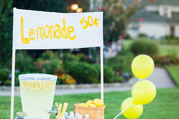 Refreshing lemonade stand A lemonade stand is set up in the front yard of a home in the suburbs. A beverage dispenser and a basket of fresh lemons are on the stand. A sign is at the top of the stand with the price of the lemonade. lemonade stand stock pictures, royalty-free photos & images