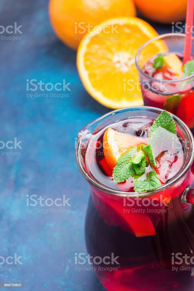 Refreshing Non-Alcoholic Spanish Sangria from Variety of Fruits Orange Citrus Pomegranate Grapes Berries and Fresh Mint in Pitcher and Tall Glass on Blue Background. Summer Vitamins Detox stock photo