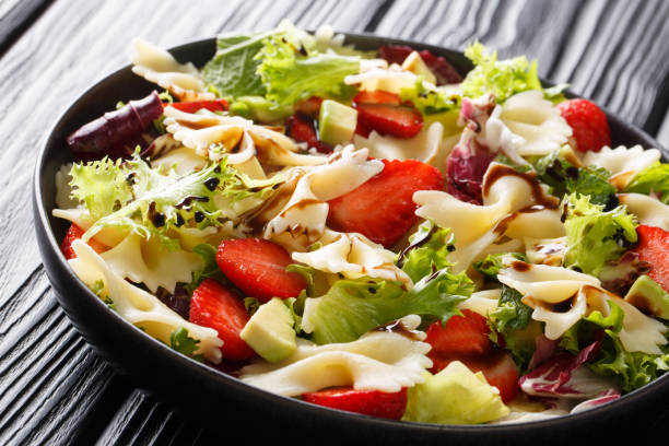Refreshing pasta salad farfalle with avocado, strawberries, lettuce and balsamic sauce close-up. horizontal Refreshing pasta salad farfalle with avocado, strawberries, lettuce and balsamic sauce close-up on a plate on the table. horizontal bow tie pasta stock pictures, royalty-free photos & images