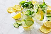 石の背景にキュウリとレモンのさわやかな夏の飲み物。食べる菜食主義者、新鮮なビタミン、自家製果実ドリンクのコンセプトです。