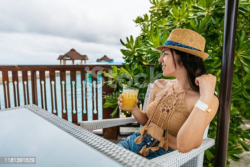 Young beautiful Caucasian woman drinking juice in cafe next to a sea on Maldives.