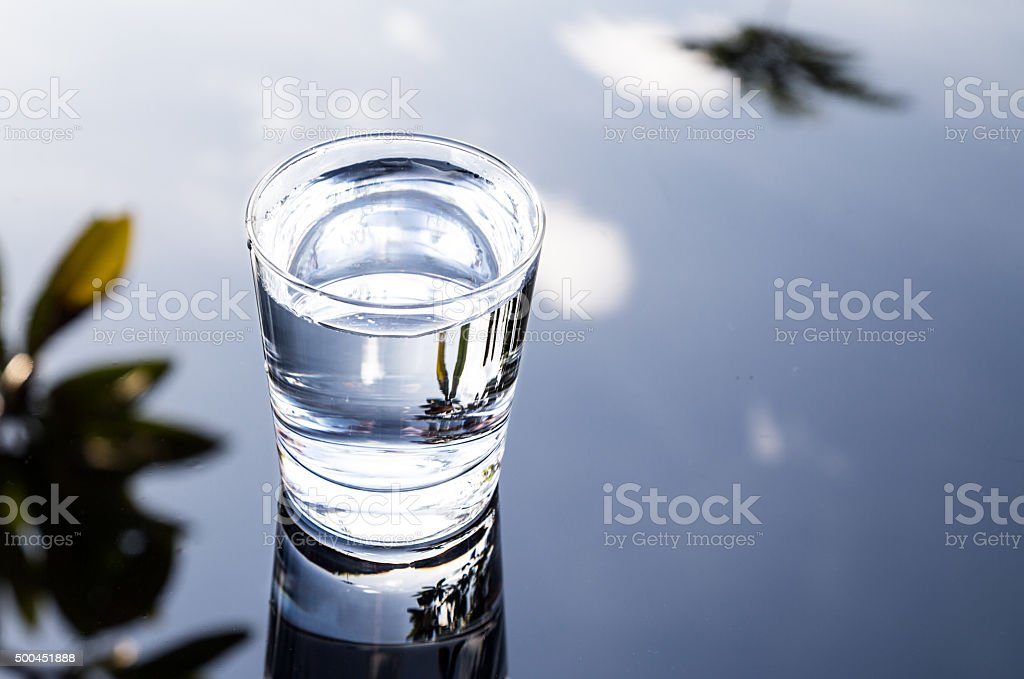 Refreshing water in transparent glass with reflection against bl stock photo