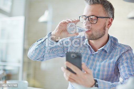 Businessman in casualwear drinking water while reading sms or dialing number on cellphone