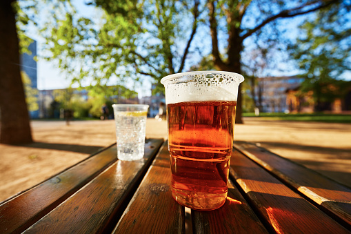 Cups of beer and water in the garden restaurant