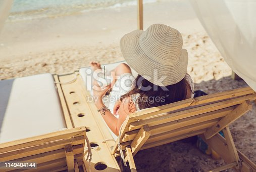 Young caucasian woman  relaxing on the beach with orange juice.