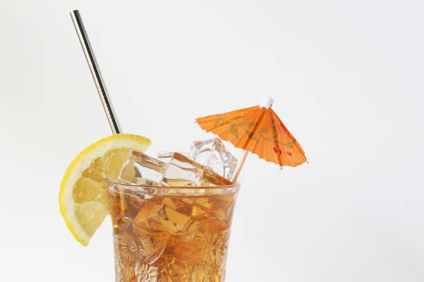 Refreshment Cold drink with lemon, umbrella and steel straw. Copy space. drinking straw stock pictures, royalty-free photos & images