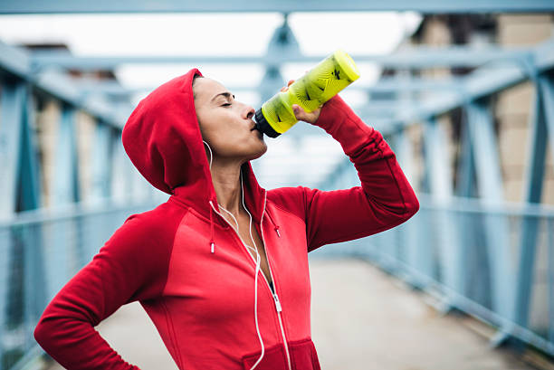 Refreshment Woman drinking water during workout tuff stock pictures, royalty-free photos & images