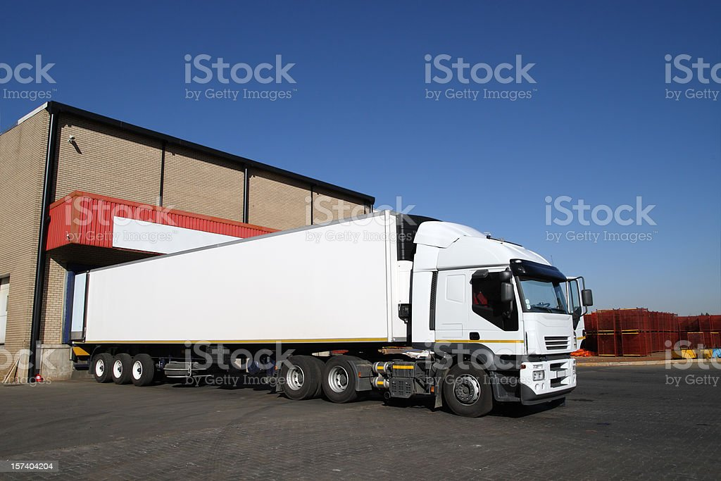Refrigerated semi truck at a cold storage warehouse loading bay. stock photo