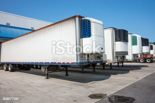 Refrigerated truck trailers lined up at a distribution warehouse.