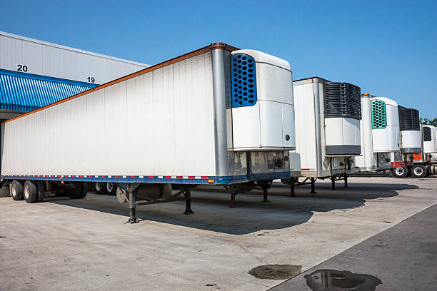 Refrigerated truck trailers at a distribution warehouse Refrigerated truck trailers lined up at a distribution warehouse. vehicle trailer stock pictures, royalty-free photos & images