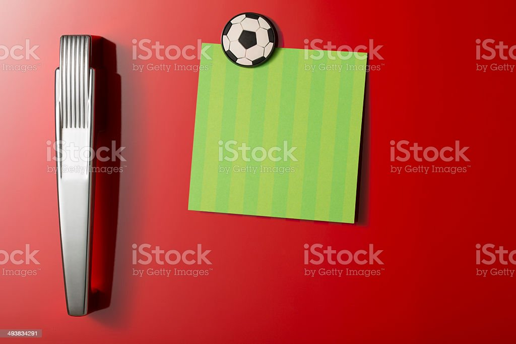 Refrigerator door with green post-it note and football magnet stock photo