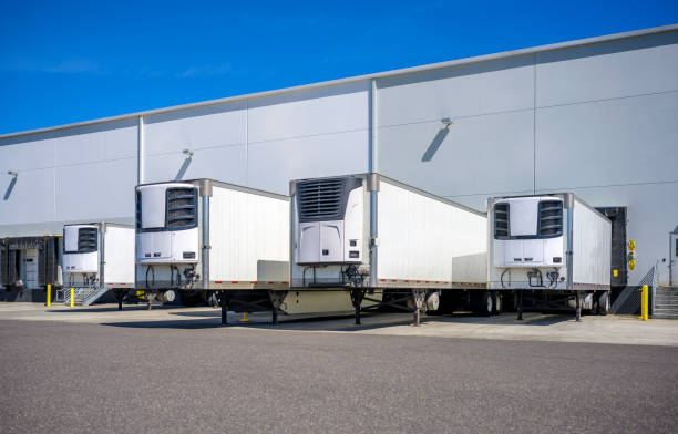 Refrigerator semi trailers without semi trucks standing at warehouse dock gates loading frozen cargo for next freight stock photo