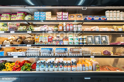Refrigerator shelves with vegetables, dairy products, meat, eggs, caviar in a grocery delicatessen store.