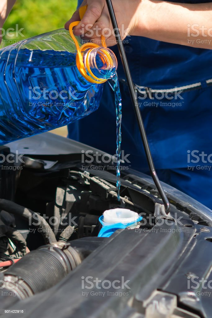 refueling the car with a glass cleaner, under the hood stock photo