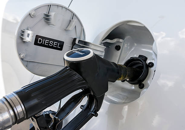 Refueling the car with diesel close up illustration. A service station gas nozzle in the fuel filling diesel onto a car. Narrow depth of field with focus on the handle. there are contrast between the white car and the black handle. diesel stock pictures, royalty-free photos & images