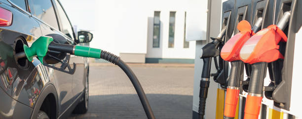 reabastecimiento de combustible del vehículo en una gasolinera - echar combustible fotografías e imágenes de stock