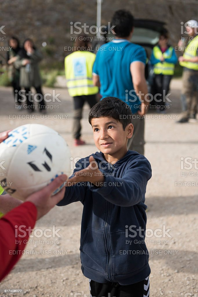 Refugee boy receives football to play with from volunteer stock photo