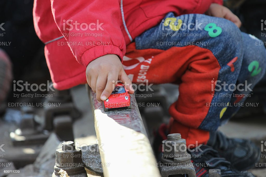 Refugee child playing with a toy car stock photo
