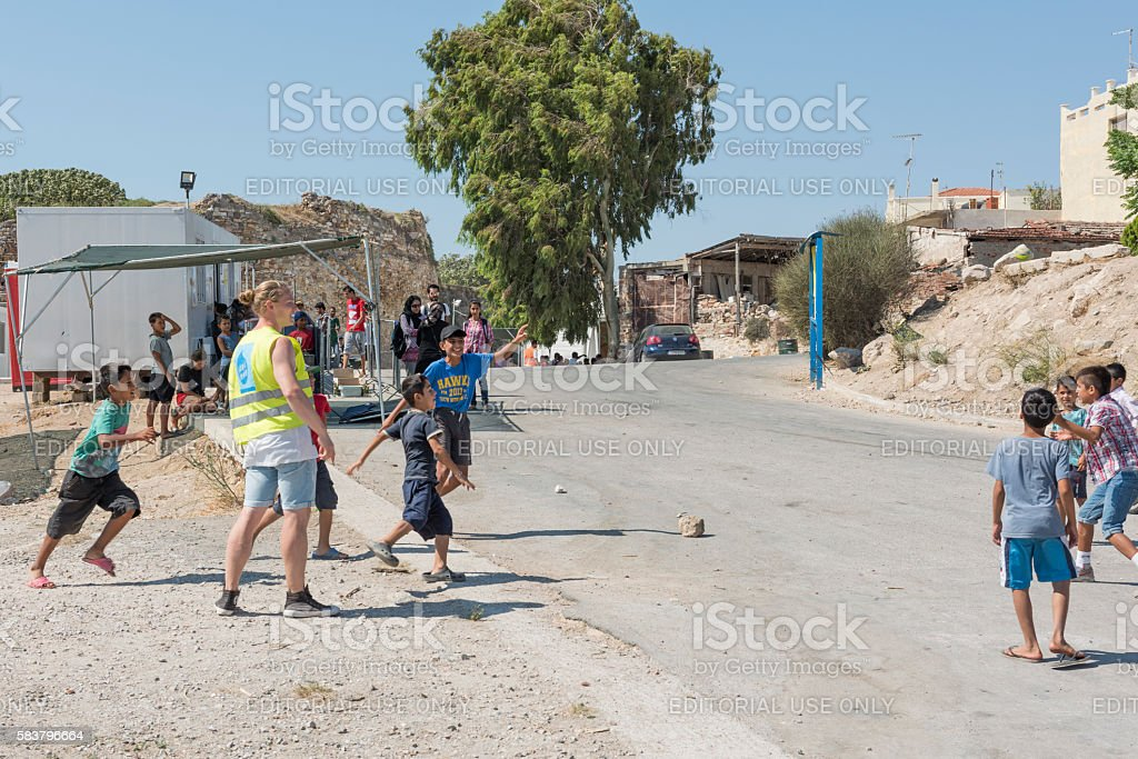 Refugee children and volunteers playing in Greek refugee camp royalty-free stock photo