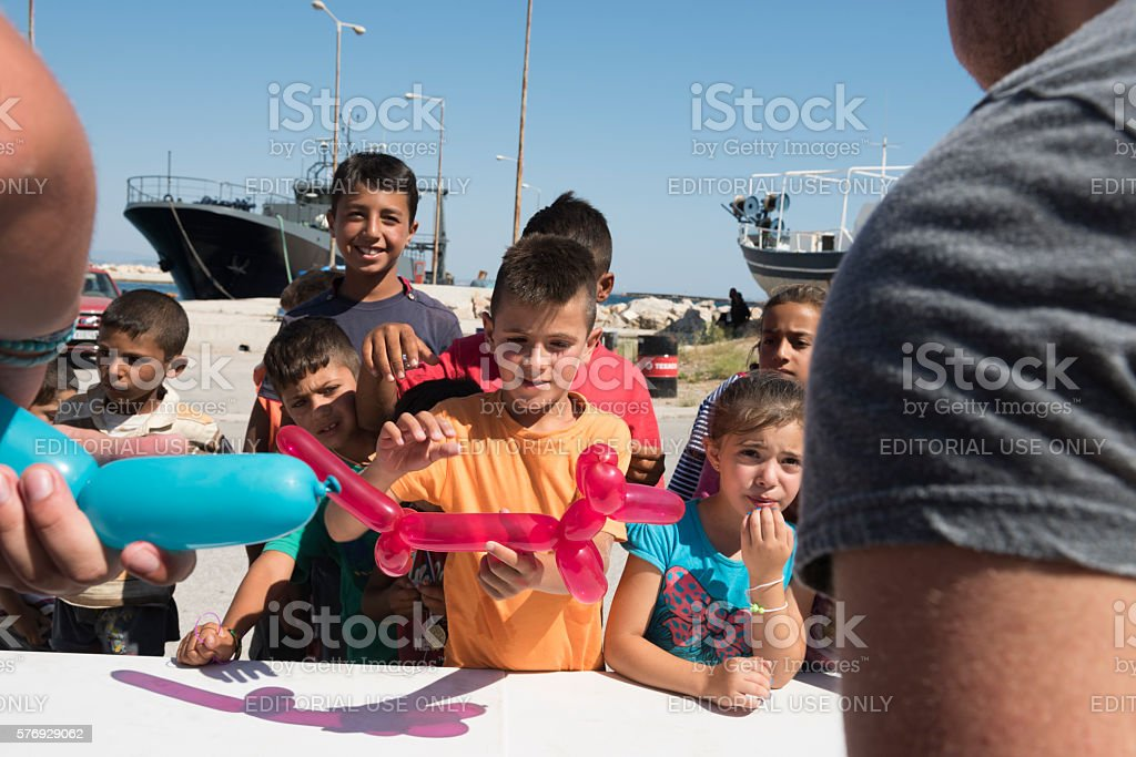 Refugee children with balloon shaped as dog stock photo