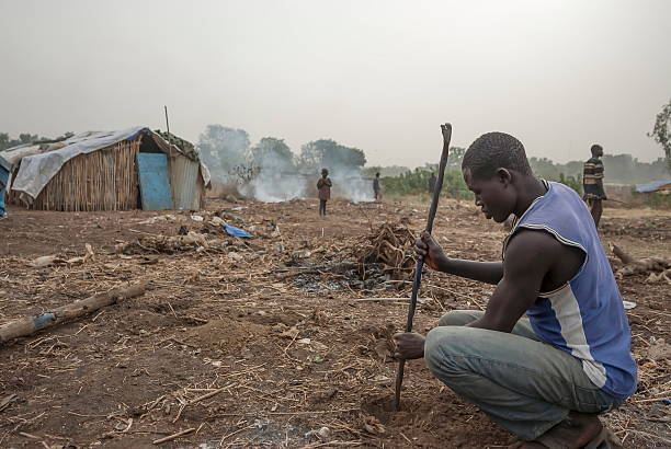 refugee digs hole in displaced persons camp, juba, south sudan. - sudan stock photos and pictures
