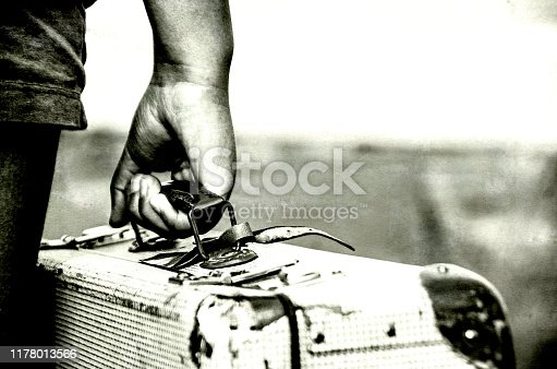 Refugee girl with her suitcase, close up BW