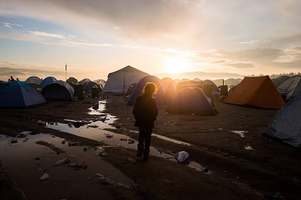 Refugee kid among tents stock photo