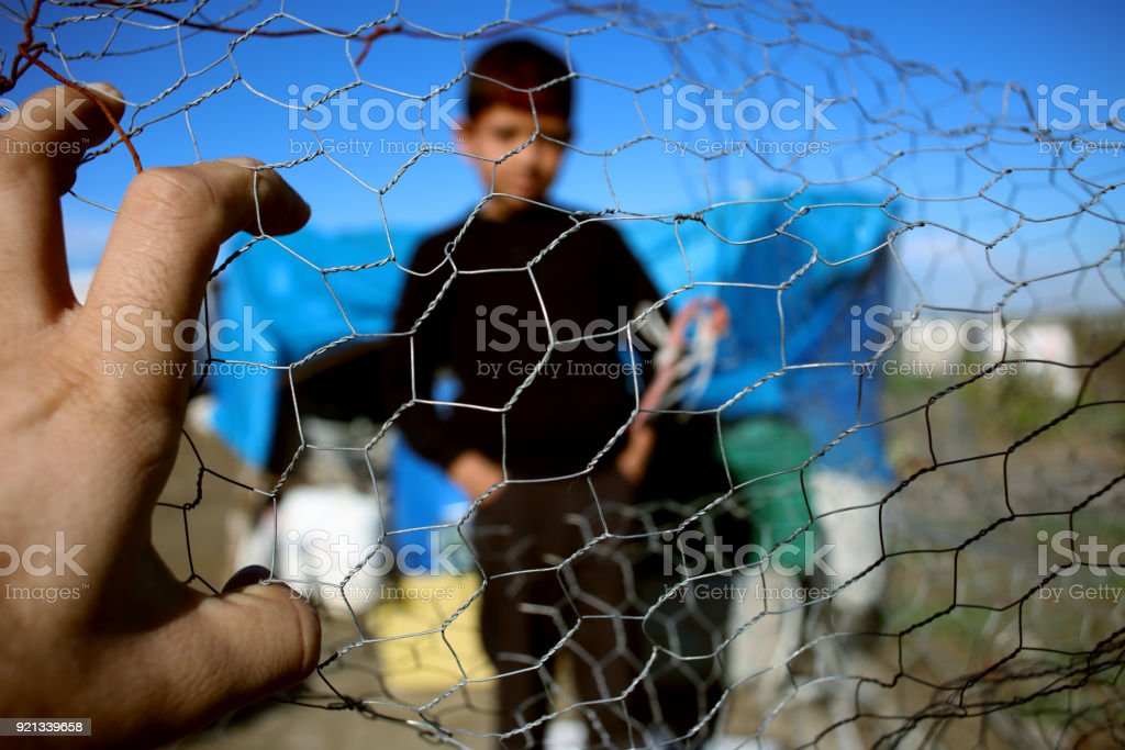 Refugee kid behind wire fence stock photo