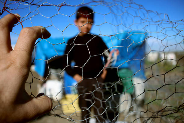 Refugee kid behind wire fence Refugee kid behind wire fence, syria, refugee camp geographical border stock pictures, royalty-free photos & images
