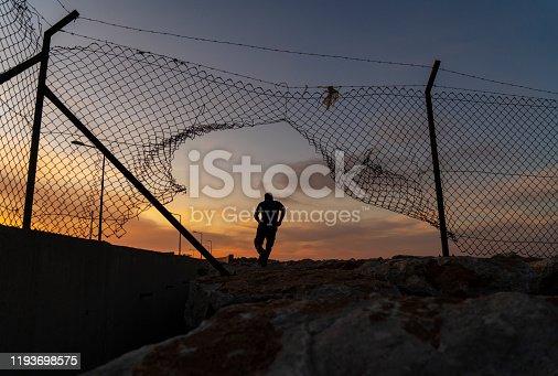 Refugee man running behind fence,