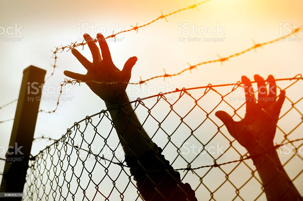 Refugee men and fence stock photo