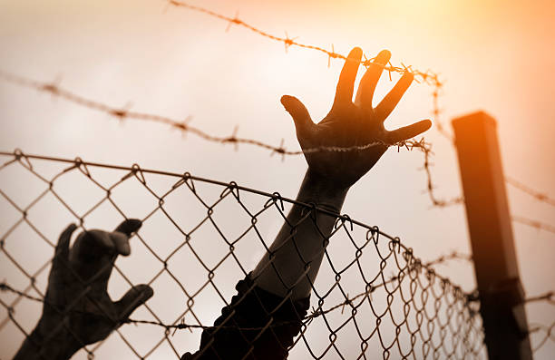 Refugee men and fence. Refugee concept Refugee men and fence. Refugee concept immigrant stock pictures, royalty-free photos & images