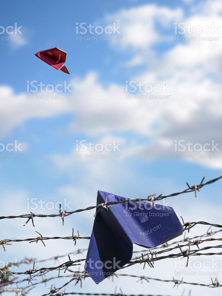 refugee passport hangs in barbed wire, an European passport flie stock photo