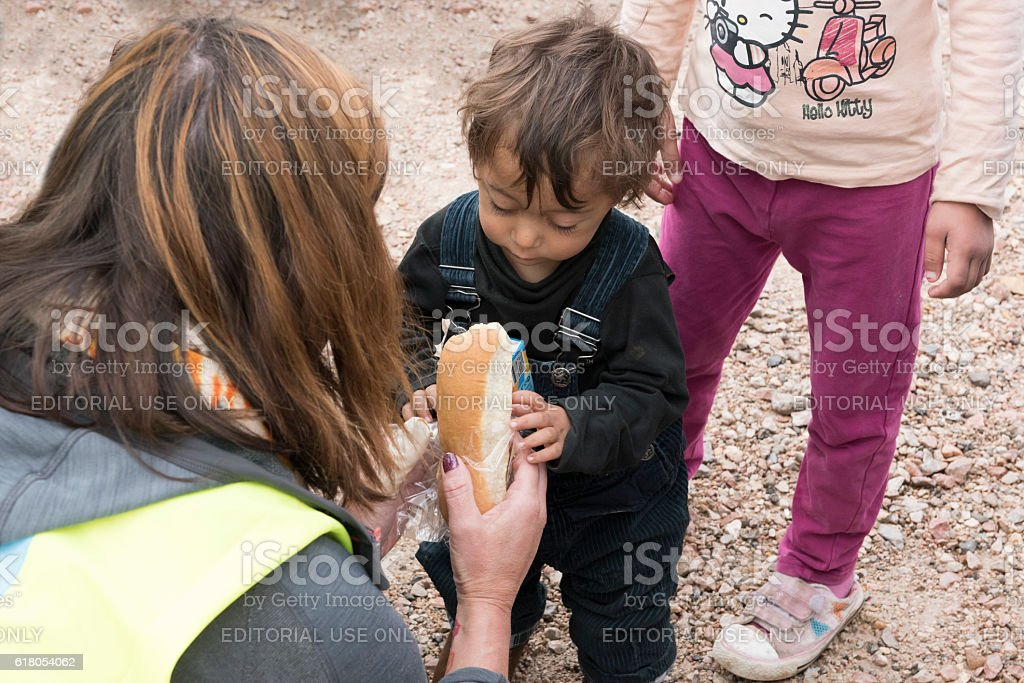 Refugee toddler with sandwich and orange juice royalty-free stock photo