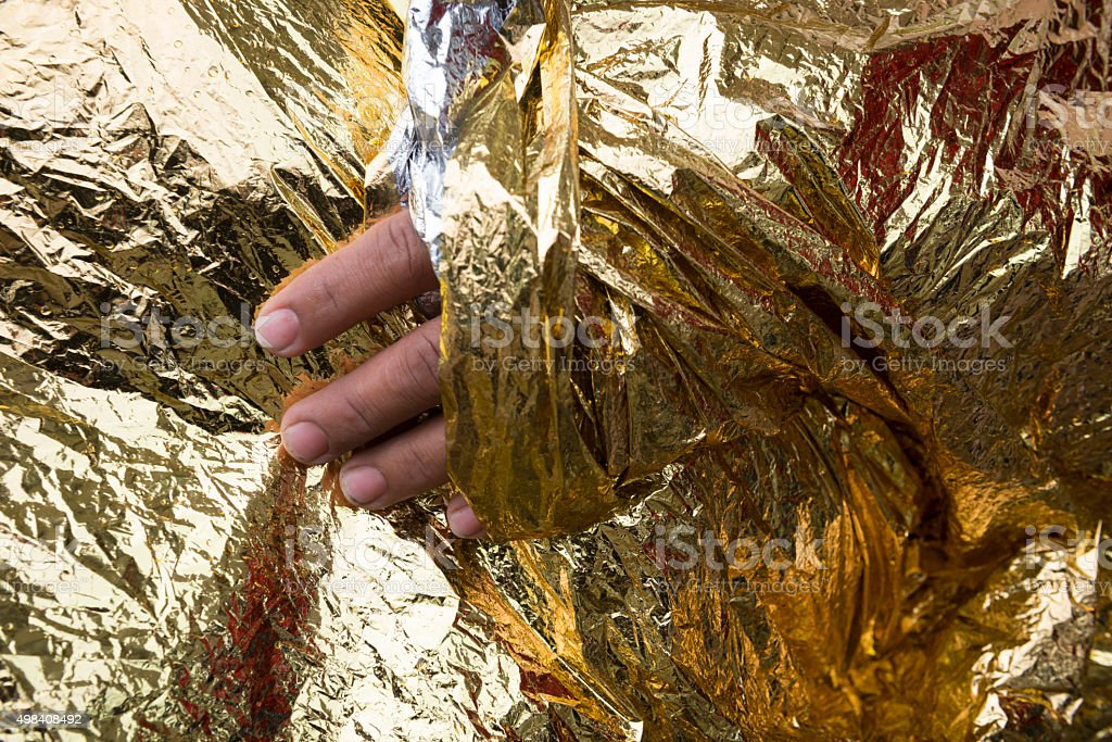 Refugee wrapped in foil blanket on Lesbos, Greece stock photo