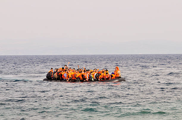Refugees arrive at Greek island Lesvos Lesvos, Greece- October 20, 2015: Refugees arriving in Greece in dingy boat from Turkey with Syrian, Afghanistan and African refugees .Their over crowded boat is still at sea an will land at the North coast of Lesvos near Molyvos, Eftalou and Skala Sikaminia. immigrant stock pictures, royalty-free photos & images