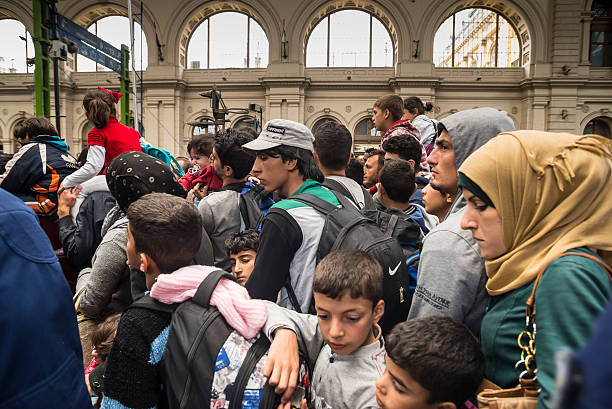 Refugees in train station stock photo