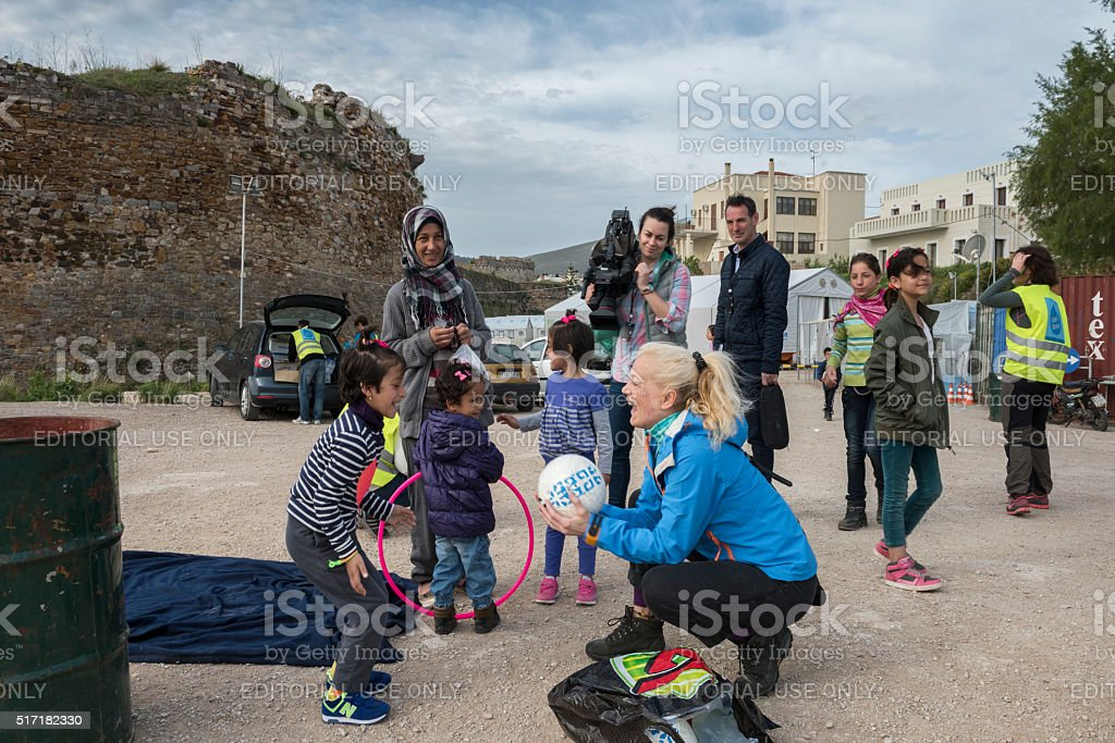 Refugees, NGO volunteers and TV team at Greek refugee camp stock photo
