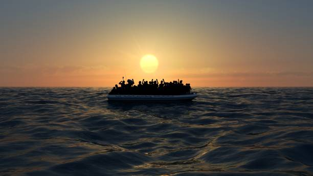 Refugees on a big rubber boat in the middle of the sea that require help Refugees on a big rubber boat in the middle of the sea that require help. Sea with people in the water asking for help. Migrants crossing the sea immigrant stock pictures, royalty-free photos & images