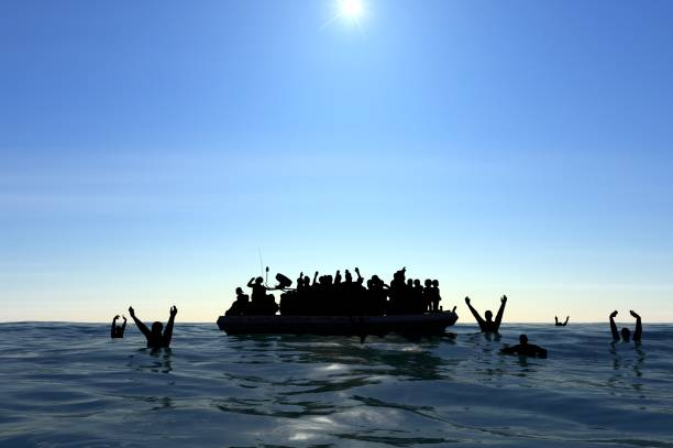 Refugees on a big rubber boat in the middle of the sea that require help stock photo