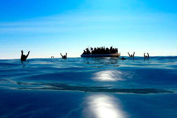 Refugees on a big rubber boat in the middle of the sea that require help. stock photo