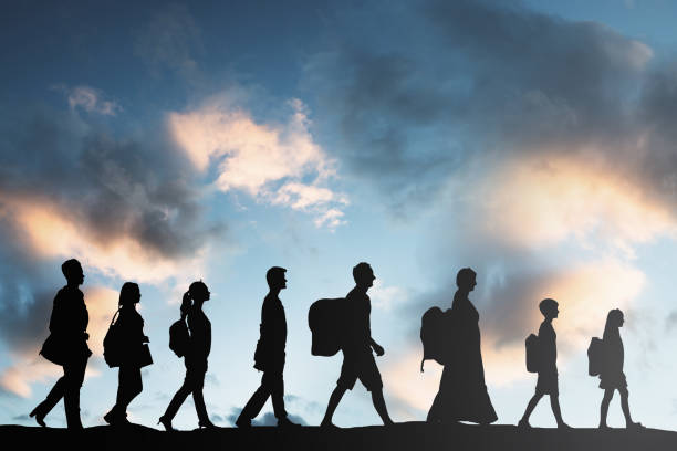 Refugees People With Luggage Walking In A Row stock photo