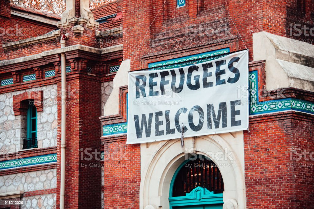 Refugees Welcome A banner hanging on a facade of a public building, belonging to the city hall, in Madrid, Spain Built Structure Stock Photo