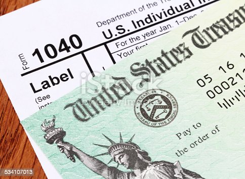 Partial view of a USA tax refund check showing the Treasury seal and image of the Statue of Liberty. Check is on top of an IRS form 1040 tax return. Shot against a wood desk background.